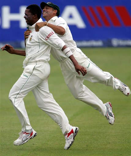 South Africa's bowler Makhaya Ntini, left, celebrates with teammate Ashwell Prince, right, after dismissing India's batsman Rahul Dravid, unseen, for 5 runs on the fourth day of the 2nd cricket Test match at Kingsmead stadium in Durban, South Africa, Friday.