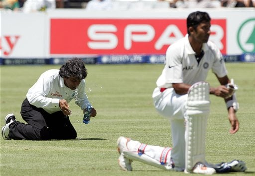 Umpire Asad Rauf of Pakistan, left, sprinkles water on his face as India's batsman Wasim Jaffer, right, awaits refreshments on the first day of the 3rd and final Test cricket match between South Africa and India at Newlands stadium in Cape Town, South Africa, Tuesday.