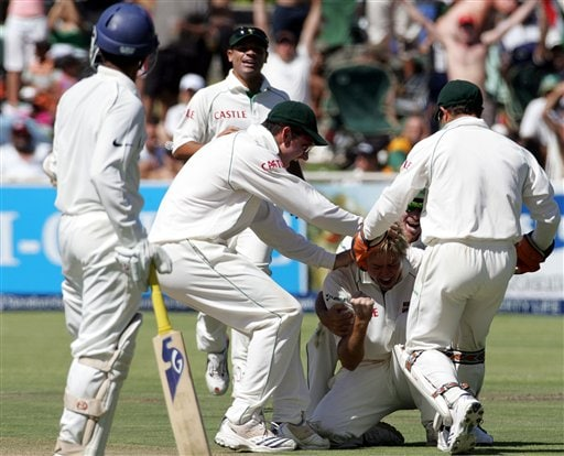 South Africa's bowler Paul Harris, center, celebrates with teammates after dismissing India's batsman Dinesh Karthik, left, for 63 runs on the first day of the 3rd and final Test match against India at Newlands stadium in Cape Town, South Africa, Tuesday.