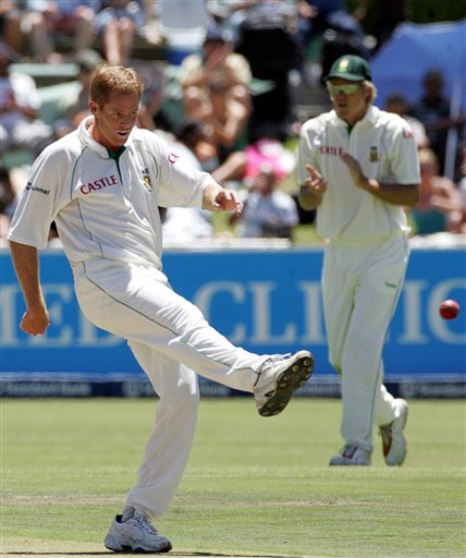 South Africa's bowler Shaun Pollock, left, kicks the ball as teammate Paul Harris, right, looks on during the first day of the 3rd and final Test cricket match against India at Newlands stadium in Cape Town, South Africa, Tuesday.