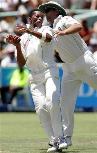 South Africa's bowler Makhaya Ntini, left, with teammate Jacques Kallis, right, fields off his own bowling on the first day of the 3rd and final Test match against India at Newlands stadium in Cape Town, South Africa, Tuesday.