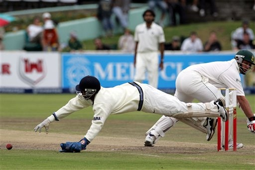 India's wicketkeeper Dinesh Karthik, left, dives as South Africa's batsman Jacques Kallis, right, looks on during the final day of the 3rd and final Test match against South Africa at Newlands stadium in Cape Town