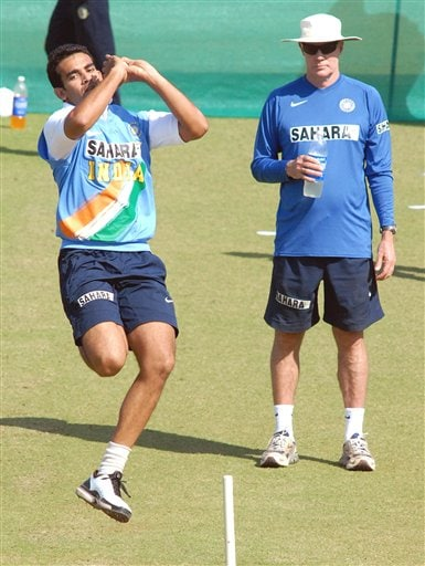 Indian cricketer Zaheer Khan bowls as coach Greg Chappell looks on during a practice session in Nagpur.