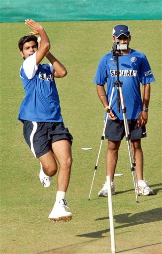 Indian cricketer R P Singh bowls, as an unidentified teammate looks through a camera, during practice session in Nagpur.