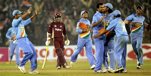 Indian cricketers, in blue, celebrate the dismissal of West Indies Daren Powel, unseen, as Powel's teammate Shiv Narain Chanderpaul looks on during the second one-day international cricket match in Cuttack.