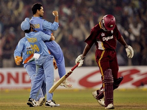 India's Sachin Tendulkar, without cap, and Dinesh Karthik, left, celebrate the dismissal of West Indies' Devon Smith, right, during the second one-day international cricket match in Cuttack.