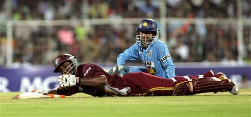 West Indies' cricketer Marlon Samuels, lying on the pitch, avoids a run out by India's wicket keeper Dinesh Karthik, in blue, during the third one-day international cricket match in Chennai, India, Saturday, January 27, 2007.