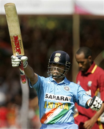 India's Sachin Tendulkar celebrates his century against West Indies during the fourth one day international cricket match in Vadodara, India.