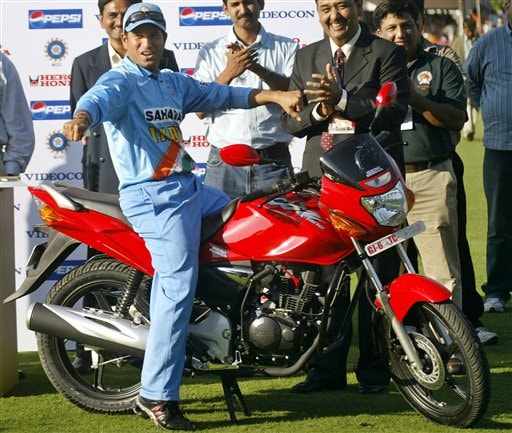 Indian cricketer Sachin Tendulkar sits on a bike he received as Man of the Match award after India won the fourth one-day international cricket match against West Indies in Vadodara, India