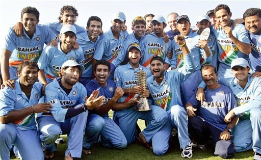 Members of the Indian cricket team pose with the winner's trophy after beating West Indies in the fourth one-day international cricket match in Vadodara, India.