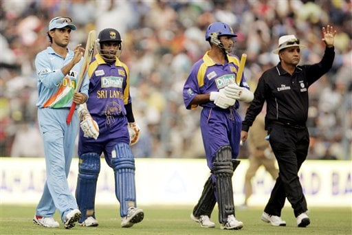 Left to right, Indian Sourav Ganguly, Sri Lankan Sanath Jayasuriya, Marvan Atapattu, and umpire Suresh Shastri leave the ground as rain falls over Eden Gardens stadium during the first one-day international cricket match between India and Sri Lanka in Kolkata on Thursday February 8, 2007.