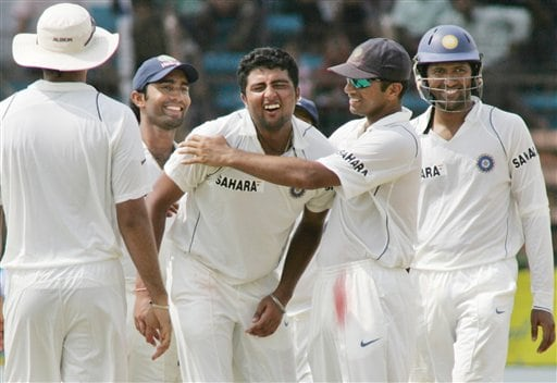 Indian bowler V.R.V. Singh, center, reacts after he received a slight injury while being congratulated by Yuvraj Singh for taking the wicket of Bangladesh batsman Khaled Mashud, unseen, on the fourth day of the first cricket test against India at the Bir Sreshta Shahid Ruhul Amin Stadium in Chittagong.