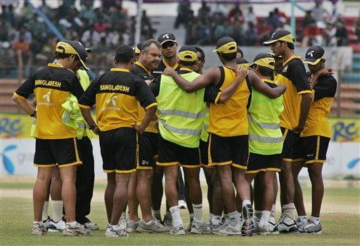 Bangladesh cricket team coach Dav Whatmore, at left facing camera, speaks to team members before a practice session on the final day of the first test match against India at the Bir Sreshta Shahid Ruhul Amin Stadium in Chittagong.