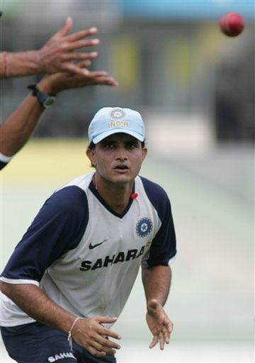 Indian cricket team member Sourav Ganguly, right, looks on as captain Rahul Dravid, hands alone visible, prepares to catch the ball during a practice session at the Shere Bangla National Stadium in Dhaka, Bangladesh, Thursday, May 24, 2007. The first test between hosts Bangladesh and India ended in a draw, the second test begins in Dhaka Friday.