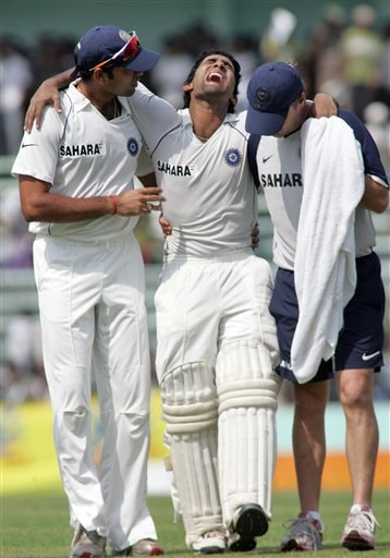 Indian batsman Dinesh Karthik, center, reacts in pain as he is carried off the pitch by teammate V V S Laxman, left, and physiotherapist John Gloster after he was injured on the first day of the second cricket test match between India and Bangladesh at the Shere Bangla National Stadium in Dhaka, Bangladesh, Friday, May 25, 2007.