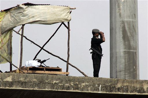 An Indian paramilitary soldier scans the stadium with a binocular as another takes position on the rooftop during the first Test cricket match between India and England in Chennai on Thursday, December 11, 2008. (AP Photo)