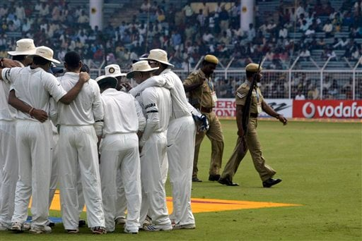 Indian cricketers huddle as two policemen walk out of field before the start of the first Test match between India and England in Chennai on Thursday, December 11, 2008. (AP Photo)