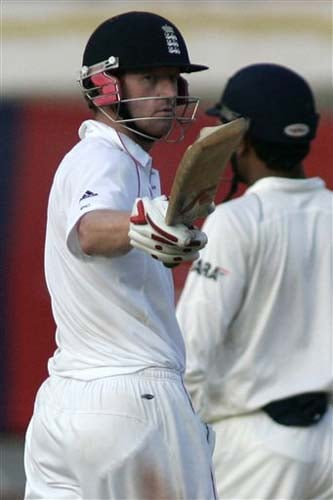 England's Paul Collingwood shows his bat to his team mates at player box after scoring fifty runs during the third day of first Test match between India and England in Chennai on Saturday.(AP Photo)