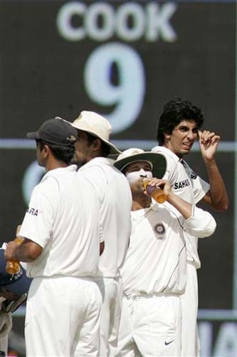 India's player Ishant Sharma, Sachin Tendulkar, and Rahul Dravid take a break after the dismissal of England's Alastair Cook during the third day of the first Test match between India and England in Chennai on Saturday. (AP Photo)