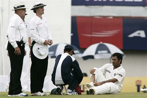 An Indian support staff helps injured MS Dhoni as umpires Daryl Harper and Billy Bowden, look on during third day of the first Test match between India and England in Chennai on Saturday.(AP Photo)