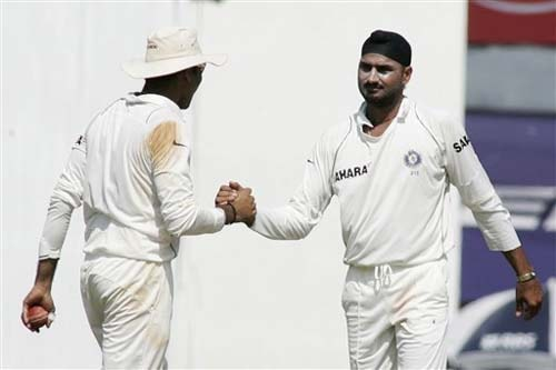 India's VVS Laxman congratulates team-mate Harbhajan Singh for taking the wicket of England's Andrew Strauss during the fourth day of the first Test match between India and England in Chennai on Sunday.(AP Photo)