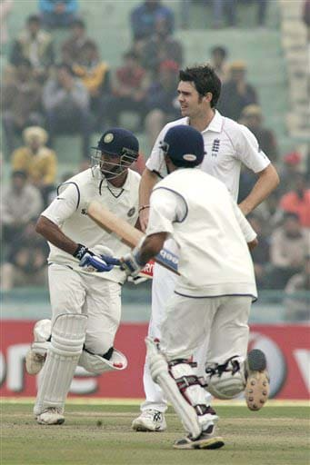 Gautam Gambhir and Rahul Dravid run between the wickets as James Anderson looks on during the second day of the second Test match between India and England in Mohali on Saturday. (AP Photo)