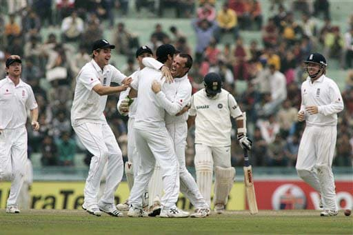 Sachin Tendulkar walks back to the pavilion as England's team celebrates his dismissal during the second day of the second Test match between India and England in Mohali on Saturday. (AP Photo)