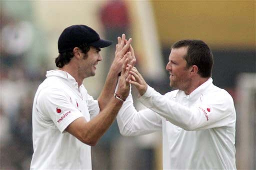 James Anderson and Graeme Swann celebrate the dismissal of Rahul Dravid during the second day of the second Test match between India and England in Mohali on Saturday. (AP Photo)