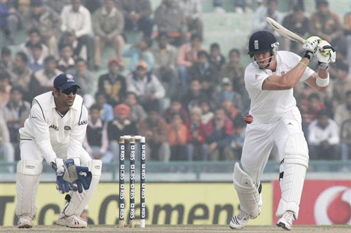 England captain Kevin Pietersen hits a shot as his Indian counterpart and wicketkeeper Mahendra Singh Dhoni takes his position during the third day of the second Test between India and England in Mohali.