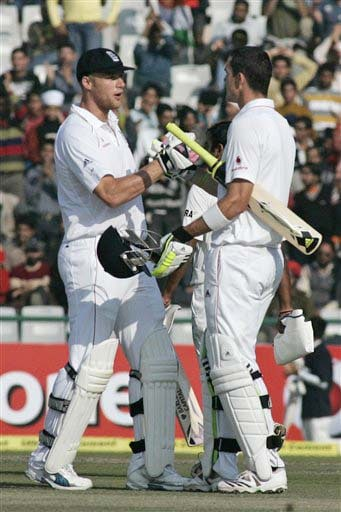 Andrew Flintoff congratulates Kevin Pietersen after the latter completed a century during the third day of the second Test match between India and England in Mohali on Sunday. (AP Photo)