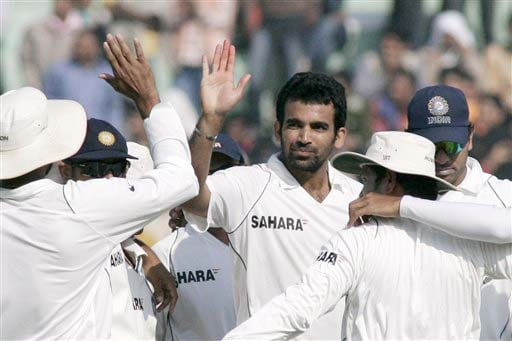 Indian cricketers congratulate team-mate Zaheer Khan after he dismissed Alastair Cook during the third day of the second Test match between India and England in Mohali on Sunday. (AP Photo)