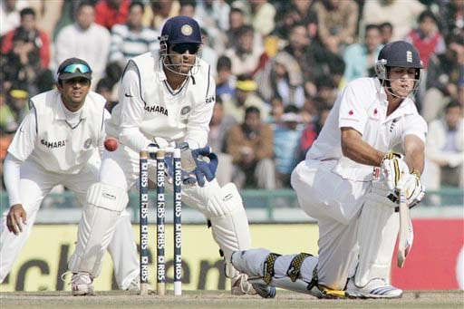 Alastair Cook hits a shot as Mahendra Singh Dhoni and Rahul Dravid look on during the third day of the second Test match between India and England in Mohali on Sunday. (AP Photo)