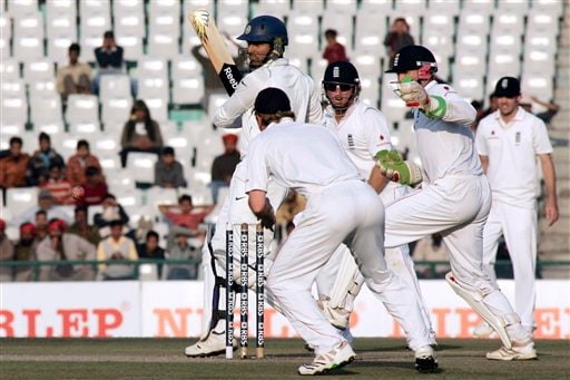 Yuvraj Singh hits a shot surrounded by England's cricketers during the fourth day of the second Test match between India and England in Mohali on Monday. (AP Photo)