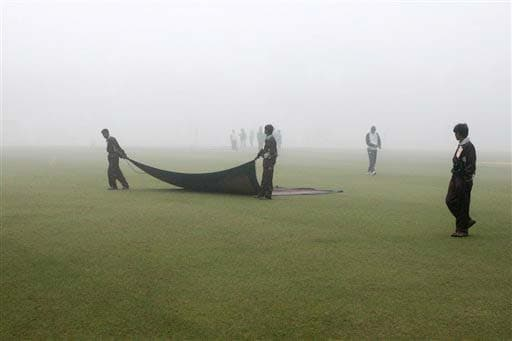 Grounds men pull rag on ground to soak dew at the start of fourth day of second Test match between India and England in Mohali on Monday. (AP Photo)