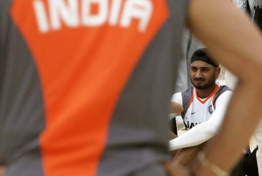 Spin bowler Harbhajan Singh of the Indian cricket team watches team mates play a game of beach volleyball game.