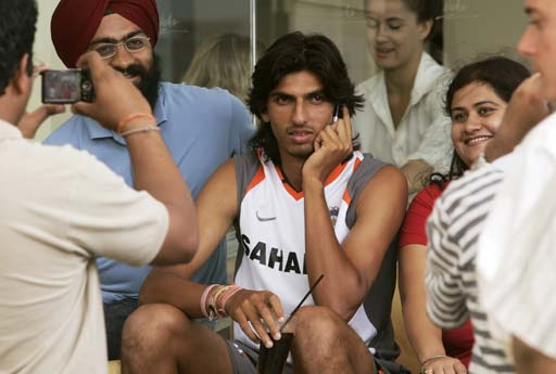 Ishant Sharma, center, tries to continue a cell phone conversation as fans pose alongside him during the team's lunch break at Sydney's Bondi Beach.
