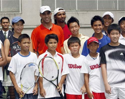 James Blake poses with children for pictures after a tennis training workshop in Kuala Lumpur on Tuesday. Blake will play against Roger Federer of Switzerland in an exhibition match later on Tuesday.