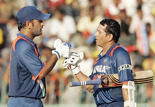 Indian captain MS Dhoni congratulates teammate Sachin Tendulkar as he completed a century during the Tri-Nation Championship Trophy final ODI match against Sri Lanka in Colombo on Monday. (AP Photo)