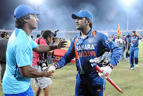 Sri Lankan captain Kumar Sangakkara is congratulated by Indian captain MS Dhoni after victory in the Tri-Nation Championship trophy final ODI match at the R. Premadasa Stadium in Colombo on Monday. (AFP Photo)