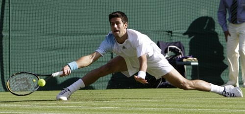 Serba's Novak Djokovic reaches for the ball during his first round match against Germany's Michael Berrer on the Centre Court at Wimbledon.