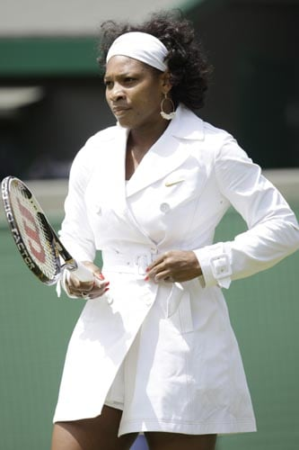 Former champion Serena Williams wears a belted raincoat while warming up for her women's singles first round match against Kaia Kanepi of Estonia at Wimbledon.