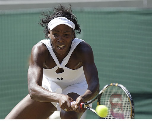 Venus Williams of the USA, returns to Thailand's Tamarine Tanasugarn during their Women's singles quarterfinal match on the Number One Court at Wimbledon.