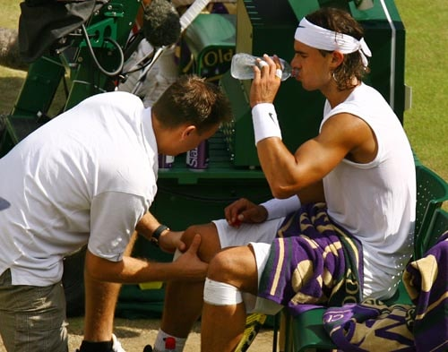 Spain's Rafael Nadal right, has his knee checked by a trainer during his match against Switzerland's Roger Federer during the men's singles final on the Centre Court at Wimbledon.