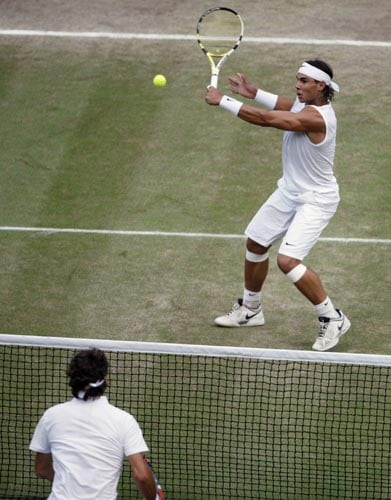 Switzerland's Roger Federer left, watches as Spain's Rafael Nadal returns the ball during their men's singles final on the Centre Court at Wimbledon.