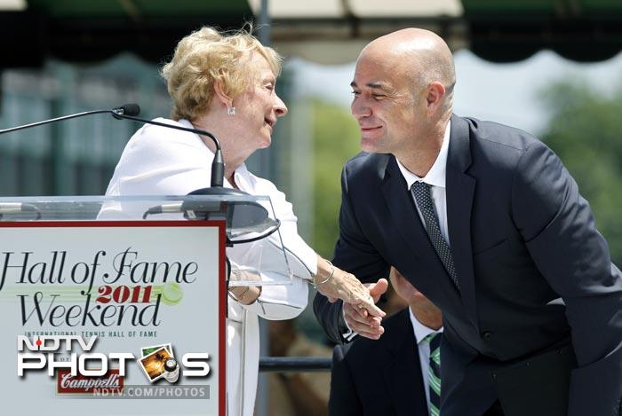 Agassi congratulates women's tennis pioneer, Peachy Kellmeyer, of the Women's Tennis Association, during her speech as they both are inducted into the International Tennis Hall of Fame in Newport. (AP Photo)