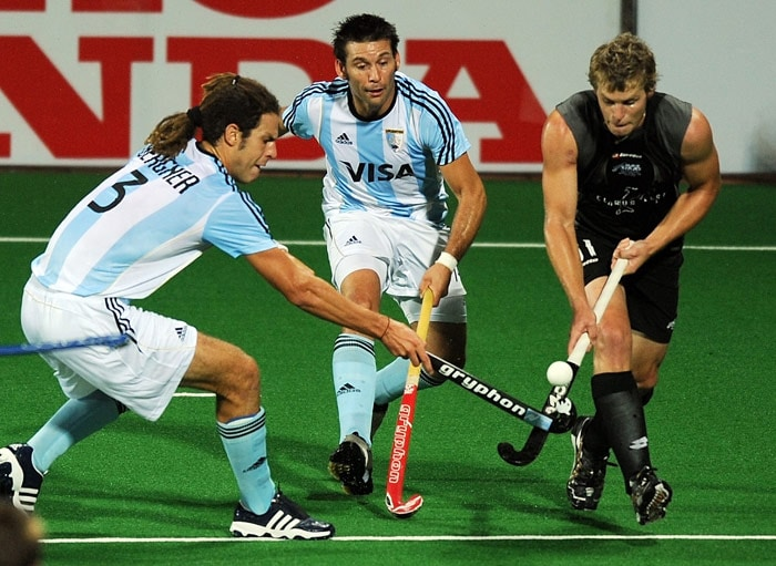 Argentinian hockey players Ignacio Ricardo Bergner (L) and Fernando Zylberberg (C) vie for the ball with New Zealand hockey player Steve Edwards (R) during their World Cup 2010 match at the Major Dhyan Chand Stadium in New Delhi. (AFP Photo)
