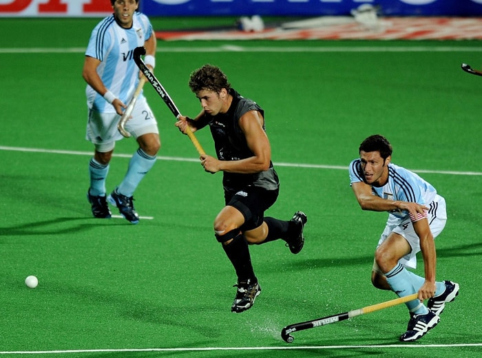 Argentinian hockey captain Matias Vila (R) vies for the ball with New Zealand hockey player Nick Wilson (C) during their World Cup 2010 match at the Major Dhyan Chand Stadium in New Delhi. (AFP Photo)