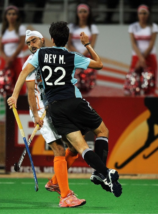 Indian hockey player Gurwinder Singh Chandi (L) vies for the ball with Argentinian Hockey player Matias Rey (R) during their World Cup 2010 Classification match at the Major Dhyan Chand Stadium. (AFP Photo)
