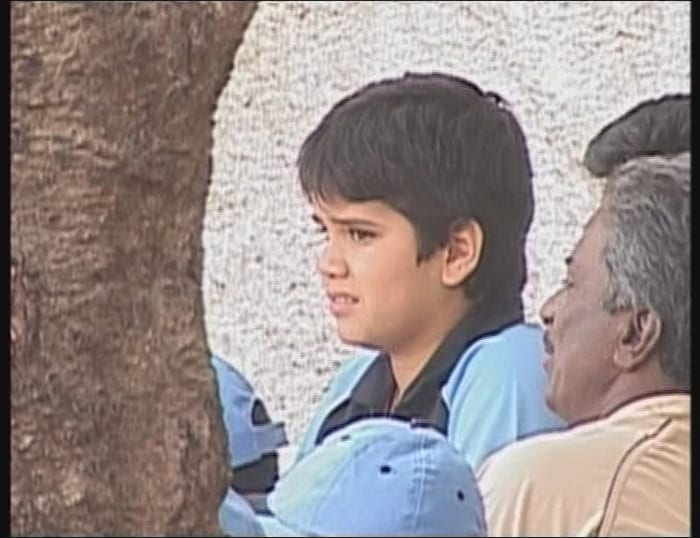 An upset Tendulkar Junior watches his team's batsmen in action after he got out after a confusion with his opening partner.