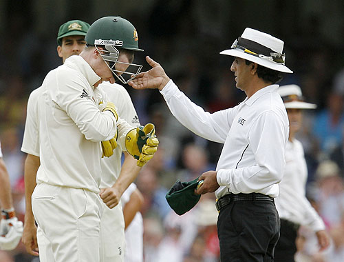 Australian wicket-keeper Brad Haddin gets help removing his helmet from Umpire Asad Rauf on the third day of the final Ashes Test match between England and Australia at the Brit Oval in London, on Saturday. (AFP Photo)